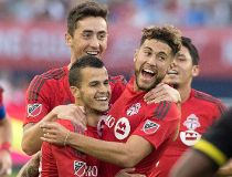Teammates celebrate with Toronto F.C.'s Sebastian Giovinco, lower left, after he scored his first of two goals during first half MLS action against Columbus Crew S.C., in Toronto on Sunday, July 31, 2016. THE CANADIAN PRESS/Fred Thornhill
