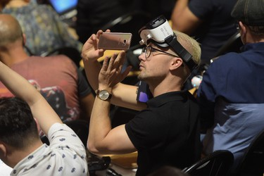 A consumer wearing a Samsung Gear VR headset takes a picture with a Samsung smartphone during Samsung Unpacked 2016 at Hammerstein Ballroom on Aug. 2, 2016 in New York City.  (Photo by Jason Kempin/Getty Images for Samsung)