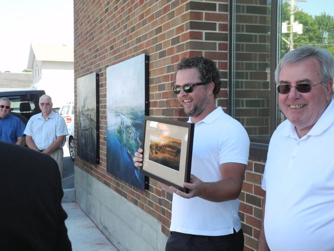 <p>Cornwall parks and recreation manager Jamie Fawthrop, left, displays one of the Cornwall Historic Walking Tour prints along with Heart of the City co-ordinator Denis Carr during the launch of the tour at the corner of Marlborough and Montreal streets on Tuesday August 2, 2016 in Cornwall, Ont. Greg Peerenboom/Cornwall Standard-Freeholder/Postmedia Network