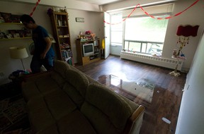 A resident walks through a partially flooded living room nearly twenty four hours after heavy rain left several units of a three storey walkup at 1170 Adelaide Street North with ankle-deep water throughout in London. (CRAIG GLOVER, The London Free Press)