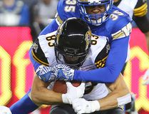 Hamilton Tiger-Cats wide receiver Andy Fantuz, left, is hauled down by Winnipeg Blue Bombers defensive back Terrence Frederick during their game in Winnipeg, on Aug. 3, 2016. (Brian Donogh/Winnipeg Sun/Postmedia Network)