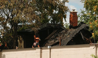 Hamilton firefighters looks at the top floor of the charred home where an early morning fire in north-end Hamilton that claimed three lives including a mother, 10-year old boy and girl under 2 years of age on Niagara St. and leaves seven other family members homeless on Saturday August 6, 2016. Jack Boland/Toronto Sun/Postmedia Network