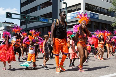 People take part during the Cariwest Festival's Great Parade along Jasper Avenue in Edmonton, Alta., on Saturday, Aug. 6, 2016. (Codie McLachlan/Postmedia)
