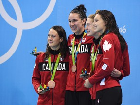 The Canadian women's 4x100-metre freestyle relay team, left to right, Sandrine Mainville, Chantal van Landeghem, Taylor Ruck and Penny Oleksiak receive their bronze medal at the 2016 Summer Olympics, in Rio de Janeiro, Brazil, on Saturday, Aug. 6, 2016. (Frank Gunn/The Canadian Press)
