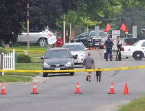 Police gather evidence outside of a house in Strathroy Ont.