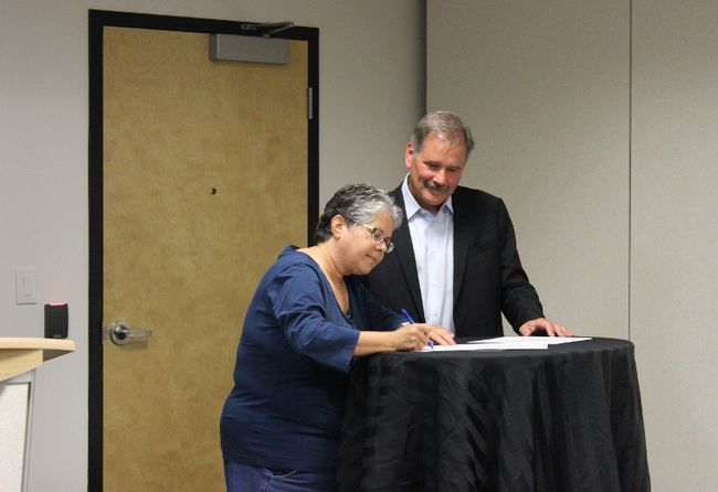 Métis Local 1935 president Gail Gallupe signs an agreement with Careers president and CEO, Andy Neigel on Tuesday. The agreement is to ensure aboriginal youth in Wood Buffalo are part of the workforce. Stephanie Jellett/Fort McMurray Today/Postmedia Network