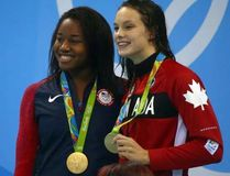 Simone Manuel (left) of the United States and Penny Oleksiak (right) of Canada tie for gold in the 100m Freestyle final during the 2016 Rio Olympics in Rio de Janeiro, Brazil on Thursday Aug. 11, 2016.