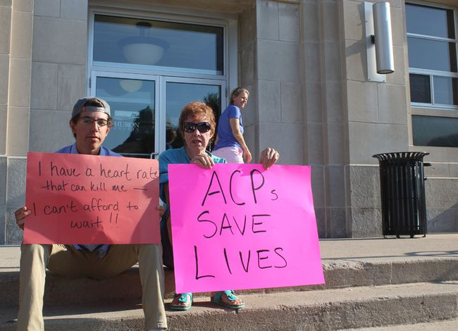 Matthew Lloyd and Ruthann Knight sit on the steps of the Huron County Courthouse as a part of a larger group protesting the elimination of the Advanced Care Paramedic program on Aug. 10. (Laura Broadley/Goderich Signal Star)