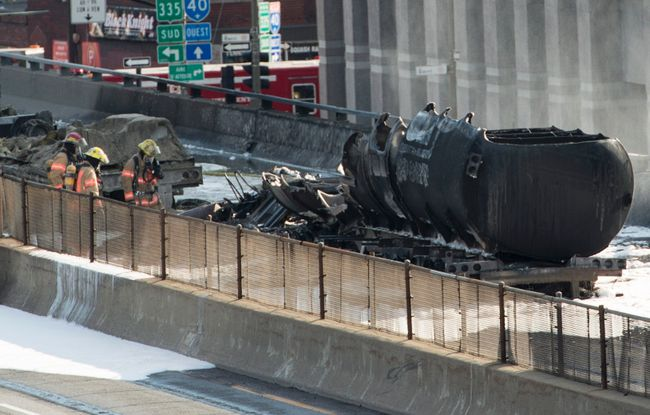 Firefighters stand next to a fuel tanker that burst into flames on autoroute 40 during rush hour after colliding with at least two other vehicles Tuesday, August 9, 2016 in Montreal. THE CANADIAN PRESS/Paul Chiasson