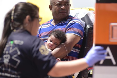 A man and his baby are transported by emergency medical personnel during a rescue operation from the burning cruise ship Caribbean Fantasy, in San Juan, Puerto Rico, Wednesday, Aug. 17, 2016. More than 500 passengers and crew are being evacuated from the burning ship about a mile off Puerto Rico's north coast. Many required medical care, though there were no reported fatalities. The fire continued to burn aboard the Caribbean Fantasy, a combination cruise and ferry ship, as the U.S. Coast Guard brought passengers into the San Juan harbor. (AP Photo/Carlos Giusti)