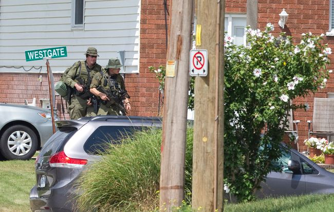 OPP officers carry rifles as they walk around the corner of a home at the corner of Park Street and Westgate Avenue, near a home at 212 Park Street where terrorism suspect Aaron Driver was shot and killed by police, in Strathroy. (CRAIG GLOVER, The London Free Press)
