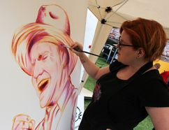 "Sarnia artist Cat Cabajar paints a portrait of Tragically Hip front man Gord Downie during That Night in Sarnia held in Canatara Park Saturday. About 10,000 people attended the local viewing party to watch The Hip's final concert in the ""Man Machine Poem"" tour being broadcasted live from Kingston. (Barbara Simpson/Sarnia Observer)"