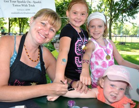 """A """"Cornfest"""" Kids Carnival was held at Keterson Park last Saturday, Aug. 20, during which donations were collected for the new Main Street United Church building. Pictured, Trish Laliberte (left) of Sparkle Tattoo Inc. applies a sparkle tattoo to Chloe Illman's arm, while Ashley McLeod and Aubrey Vosper show off Laliberte's previous work. The Mitchell Grizzlies slo-pitch team paid to have Sparkle Tattoo Inc. at the carnival, and a portion of Laliberte's proceeds from the carnival will go back to Main Street United Church. GALEN SIMMONS MITCHELL ADVOCATE"""