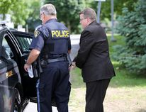 Kevin Wagar is loaded into a waiting police car after he was sentenced to five and a half years in prison for fraud. (Meghan Balogh/Postmedia Network)