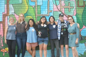 Left to right, Taylor Burnett, artist mentor, Selena Wells, artist mentor, and students Melissa Colindres, Dana Cosman, Shuko Wada, Brooke Watson and Miranda Houben stand in front of their completed mural project. (Photo courtesy of Reileigh Biggs)