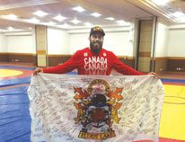 Photo supplied Korey Jarvis is a graduate of Elliot Lake's Gladiators Wrestling Club. He is holding an Elliot Lake flag signed by many local residents.