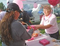 Jan Fraser serves up a burger bun with a pink napkin Thursday during the visit of the Wild Pink Yonder riders. Stephen Tipper Vulcan Advocate