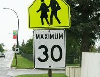 School crosswalk sign with speedlimit posted on 113 St. in Fairview
