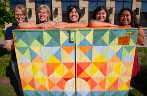 Selena Wells, Taylor Burnett, Shuko Wada, Dana Cosman and Melissa Colindres pose with a Bell telephone box they have painted near the big box stores in Hyde Park in London, Ont. on Tuesday August 23, 2016. (MIKE HENSEN, The London Free Press)