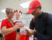Kirstin Daley holds her daughter Lyla Wheeler, 6, as Damian Warner, Olympic bronze medalist in the decathlon signs her Canadian flag in London airport upon his arrival home on Wednesday August 24, 2016. (MIKE HENSEN, The London Free Press)
