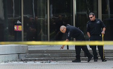 Members of the police bomb unit investigate after a small explosion outside the Law Courts building in Winnipeg on Wed., Aug. 24, 2016. Kevin King/Winnipeg Sun/Postmedia Network