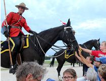 RCMP Const. Steve James, of Sarnia, Ont. smiles as Avery Vanderweide, 7, top right, of Chatham, was among those who took the opportunity to pet his horse Royal, an 18-year-old mare, after the RCMP Musical Ride at the Dresden Raceway in Dresden, Ont. on Wednesday August 24, 2016. Ellwood Shreve/Chatham Daily News/Postmedia Network