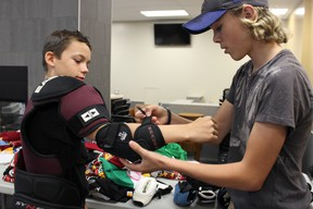 Samantha Reed/The Intelligencer  Thirteen-year-old Jacob Mattice gets outfitted with hockey equipment by volunteer Zack Goodfellow on Wednesday afternoon during the Build A Player Program event at the Quinte Sports and Wellness Centre.