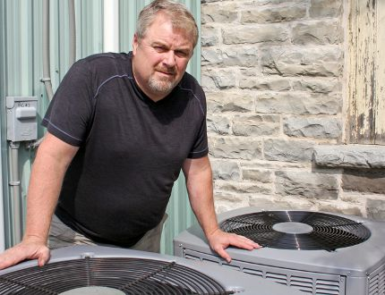 John Beskers, acting-president of the Storrington Lions Club, at the club's air conditioning units in Inverary. (Steph Crosier/The Whig-Standard)