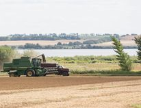 A combine unloads a hopper full of grain into the box of a farm truck so it can be hauled from the field to nearby granaries. Motorists are reminded to be aware that slower moving farm equipment is often encountered on Peace Country roads. Please be patient and allow plenty of room to pass when it is safe to do Randy Vanderveen/Special to Peace Country Sun