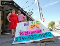 Optician Gayle Harrison and owner Rob Moffatt stand near a homemade sandwich board advertising their store, Eyes On Richmond, at the side of Richmond Street in London, Ont. on Friday August 26, 2016. Moffatt was among the 25 downtown store owners who had their signs taken by bylaw officers earlier this year during a crack down on sign infractions. (CRAIG GLOVER, The London Free Press)