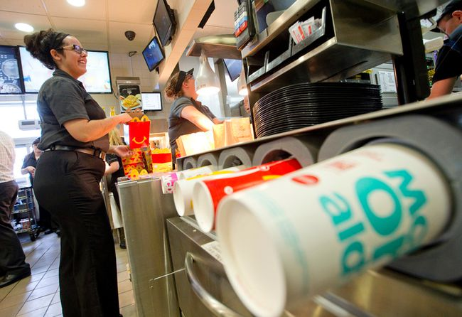 McDonald's manager Ashley Catala, who has been in management with the company for five years, helps pack happy meals at the restaurant located at Highbury Avenue and Hamilton Road, in London, Ont. on Friday August 19, 2016. (CRAIG GLOVER, The London Free Press)