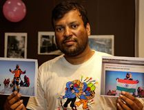In this July 4, 2016 file photo, Indian climber, Satyarup Sidhantha holds on his right hand a photograph that shows him on Mount Everest, along with what he says is an altered version of the same used by an Indian couple to make it appear they were on the summit, as he displays them for the Associated Press in Kolkata, India. Nepal mountaineering authorities have determined that an Indian couple faked a Mount Everest ascent earlier this year by altering photographs to show they were on the summit. (AP Photo/ Bikas Das, File)