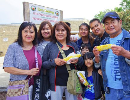 The Macainan family enjoys free corn at the 50th Morden Corn and Apple Festival Aug. 27, 2016.