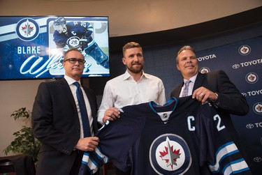 Winnipeg Jets head coach Paul Maurice, left to right, forward Blake Wheeler and general manager Kevin Cheveldayoff pose for a photo after Wheeler was named the new captain of the Jets during a press conference in Winnipeg on Wednesday, August 31, 2016. THE CANADIAN PRESS/David Lipnowski
