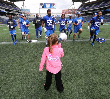 Gymnast Stephanie Gatin, 7, instructs a group of Winnipeg Blue Bombers during practice at Investors Group Field in Winnipeg on Wed., Aug. 31, 2016. The Panthers Gymnastics Club member was given the opportunity through Barbie's You Can Be Anything campaign. Kevin King/Winnipeg Sun/Postmedia Network