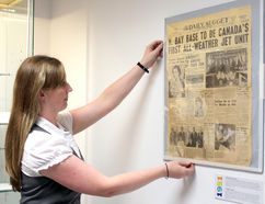 Bethany Aitchison, curator at the Canadian Forces Museum of Aerospace Defence at 22 Wing-CFB North Bay, straightens a copy of The Daily Nugget, Wednesday. The museum has a special display starting today and continuing to the end of the year marking the 65th anniversary of the base. PJ Wilson/The Nugget