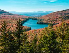 In this October 2014 photo provided by Scott McCracken, breathtaking fall foliage in Groton State Forest in Vermont is shown from Owls Head Mountain. Kettle Pond is seen in the distance. (Scott McCracken/www.scottmccracken.net via AP)