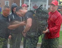 Capt. Harold Morrison, centre, gets help with his rucksack shortly after being the first to cross the finish line during the non-competitive portion of the 33rd annual 2 Canadian Mechanized Brigade Group Ironman Competition, held Thursday. The competitive race is being held the next day.