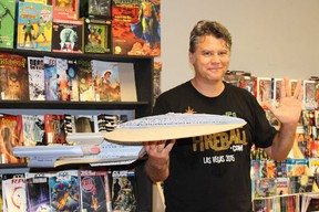 Trent Rogers flashes the Vulcan salute while holding a model of the Starship Enterprise at Future Pastimes Friday. A diehard Trekkie, Rogers estimates he owns more than 200 Star Trek books and more than 300 comics from the popular science fiction franchise. (Barbara Simpson/Sarnia Observer)