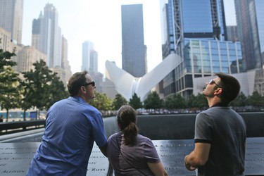 Visitors to the National September 11 Memorial take in the view from the north pool, Saturday, Sept. 10, 2016, in New York. Sunday marks the 15th anniversary of the attacks on the World Trade Center. (AP Photo/Mary Altaffer)