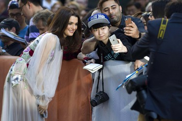 """Rachel Weisz poses for a photo with a fan before making her way towards the red carpet for the film """"Denial"""" during the 2016 Toronto International Film Festival in Toronto on Sunday, Sept. 11, 2016. (Chris Young/The Canadian Press via AP)"""