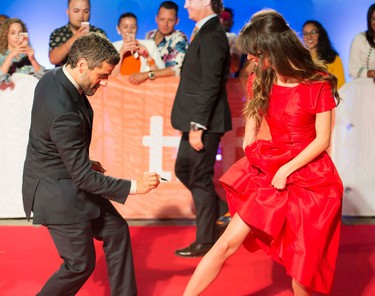 """Oscar Isaac, left, jokingly autographs the leg of Charlotte Le Bon as they arrive for """"The Promise"""" at the 2016 Toronto International Film Festival in Toronto on Sunday, Sept. 11, 2016. THE CANADIAN PRESS/Frank Gunn"""