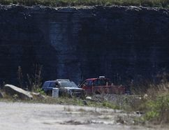 An OPP officer watches over a quarry on Amherst Island after Loyalist Township gained access to the site with a court order on Monday. (Elliot Ferguson/The Whig-Standard)