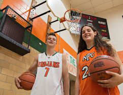 North Park Trojans senior basketball team members Ethan Andrew and Noelle Adams stand next to a shot clock (at left), which is being introduced into Ontario high school basketball this season. (Brian Thompson/The Expositor)