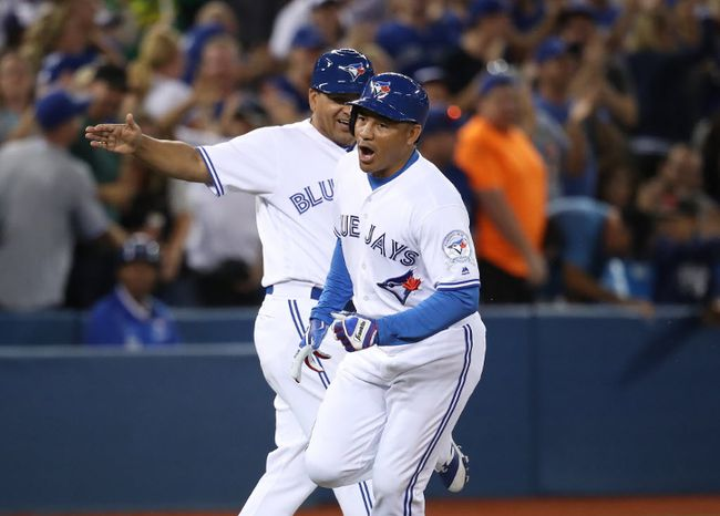 Ezequiel Carrera #3 of the Toronto Blue Jays celebrates as he is congratulated by third base coach Luis Rivera #2 after hitting a pinch-hit solo home run in the eighth inning during MLB game action against the Tampa Bay Rays on September 12, 2016 at Rogers Centre in Toronto, Ontario, Canada. (Tom Szczerbowski/Getty Images)