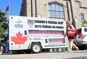 A student walks past the Canadian Taxpayers Federation's federal debt clock at Queen's University in this file photo. (Elliot Ferguson/The Whig-Standard)