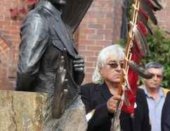 Chapleau Cree Chief Keith Corston proudly holds the Eagle Staff beside the newly unveilled Charles Byce Statue.