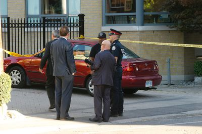 Police stand outside the lawyer's office driveway - blood from the victim is on the ground where he crawled past parked cars - after the shooting on Bedford Rd. Tuesday September 20, 2016. (Jack Boland/Toronto Sun)