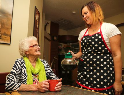 "Jennifer Liner, right, who will be taking over from Sheila Gaudet as owner of the Cross-Eyed Giraffe Cafe, serves up coffee to her first customer, 93-year-old Dora ""the explorer"" MacLean. The cafe reopened Monday morning after the last managers' lease ended in August. (Ashli Barrett, Lacombe Globe)"