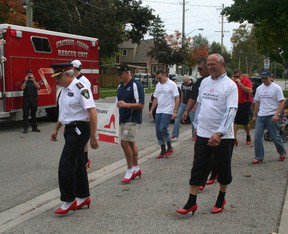 A group of men, including then Strathroy-Caradoc Police Chief Rick Beazly (left) and Lambton-Kent-Middlesex MP Bev Shipley (right), participate in the Walk a Mile in Her Shoes event in Strathroy in 2011. File photo.